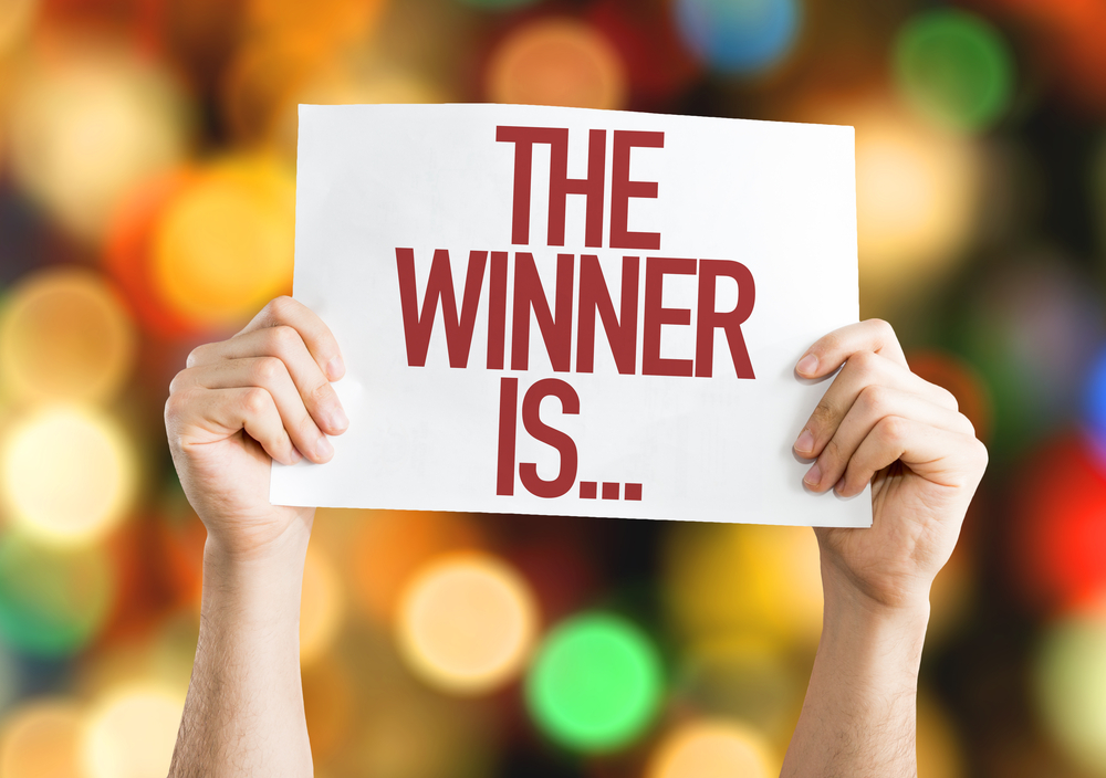 """Pair of hands hold up card with the words """"the winner is"""""""