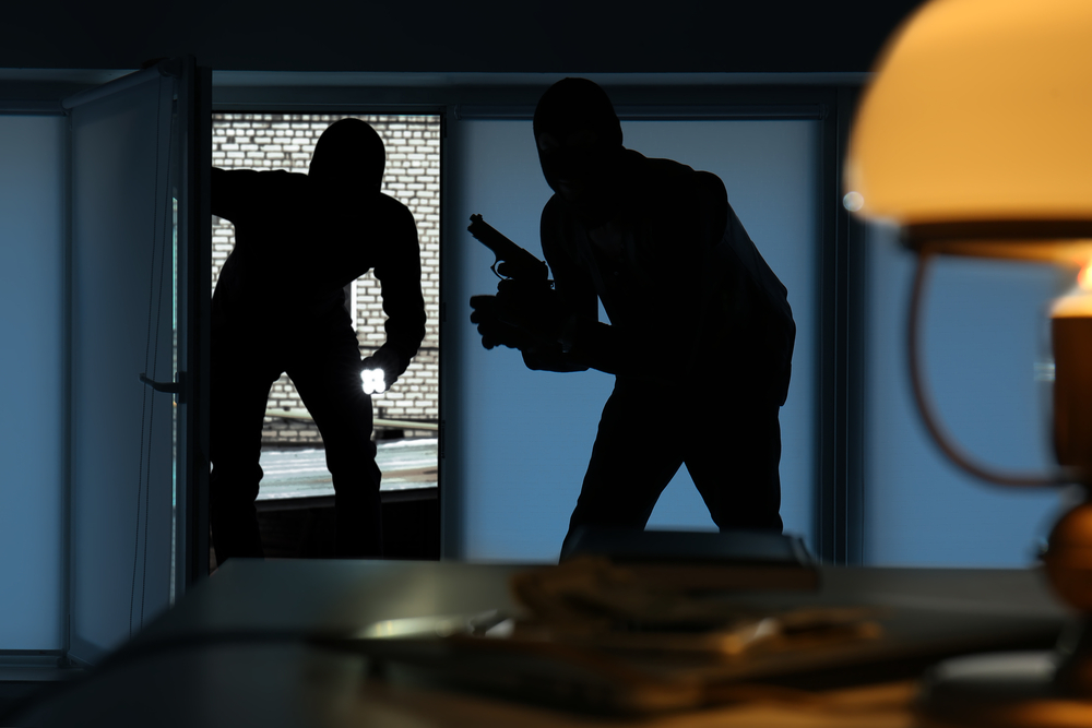 two armed burglars entering a dimly lit home