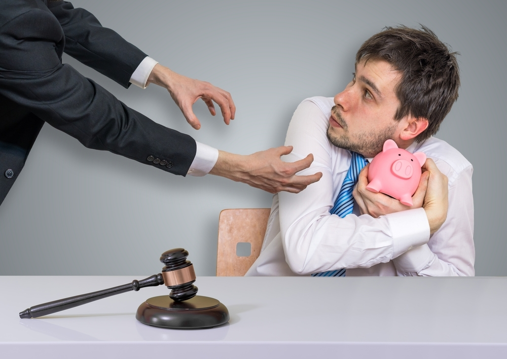 Man keeping piggy bank from businessman with gavel