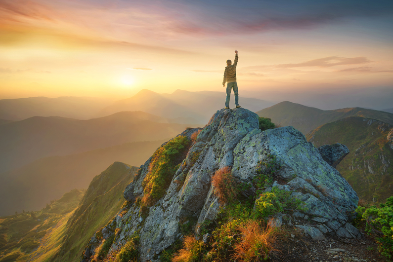 Man standing triumphant on the top of a mountain