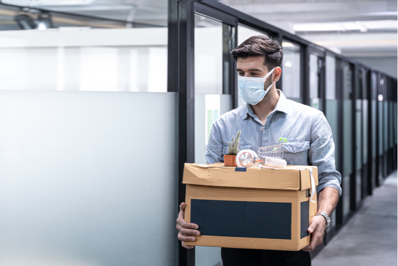 Man wearing a mask leaving an office with a box of belongings after losing his job