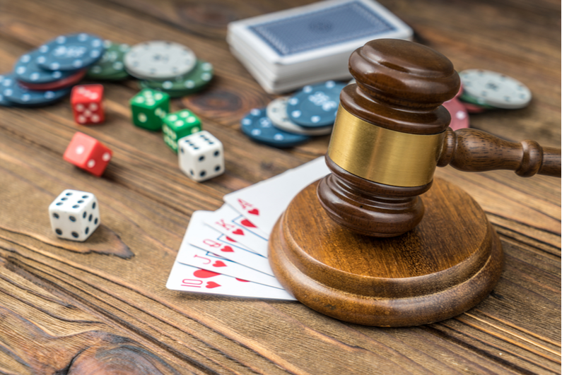 Judge's gavel with dice, chips, and cards