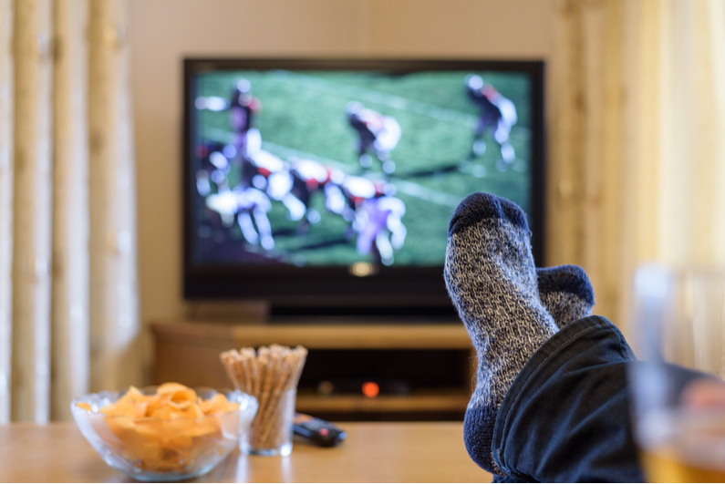 Person with their feet on a coffee table and football on TV in the background