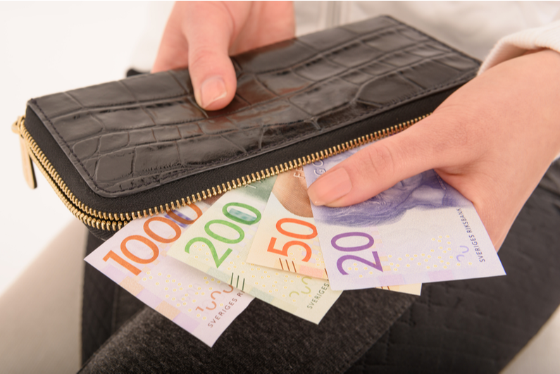 Person pulling Swedish cash out of a wallet