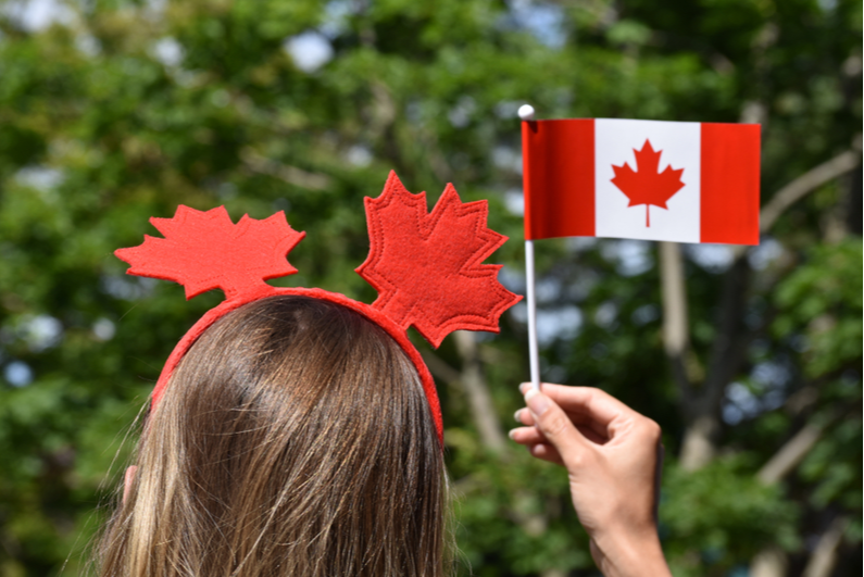 Woman wearing a red maple leaf headband and holding small Canadian flag