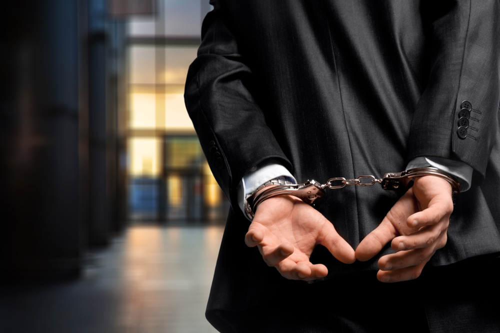 man in suit with handcuffed wrists
