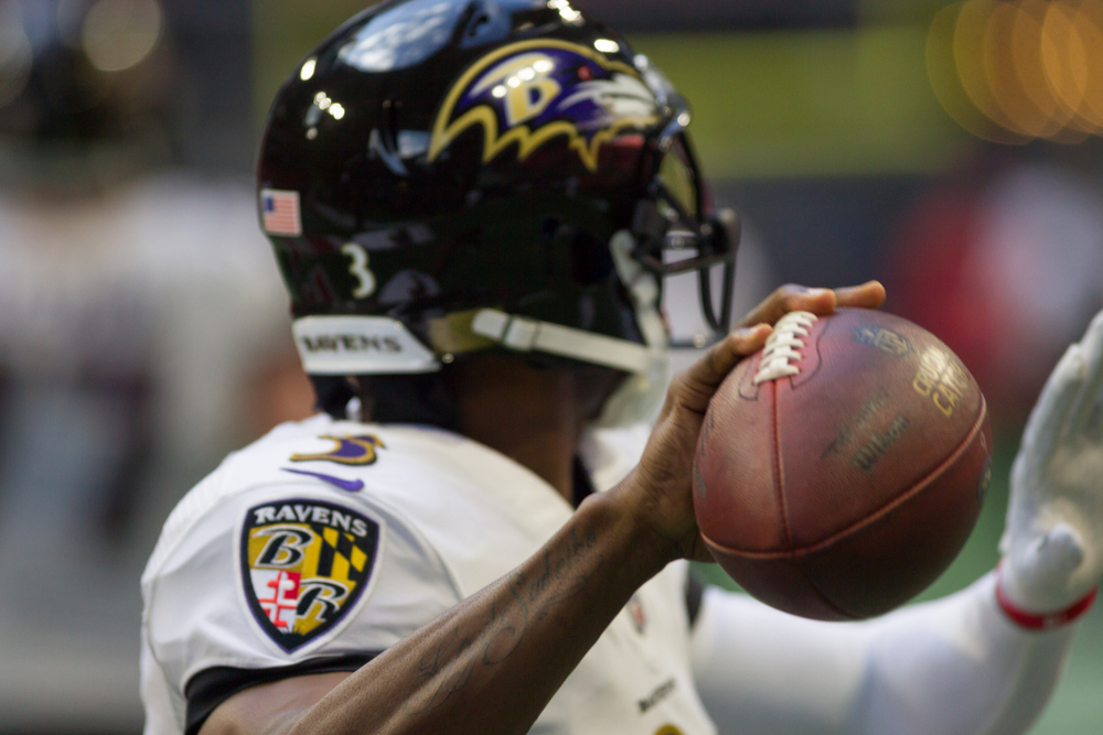 Baltimore Ravens player holding a football in one hand