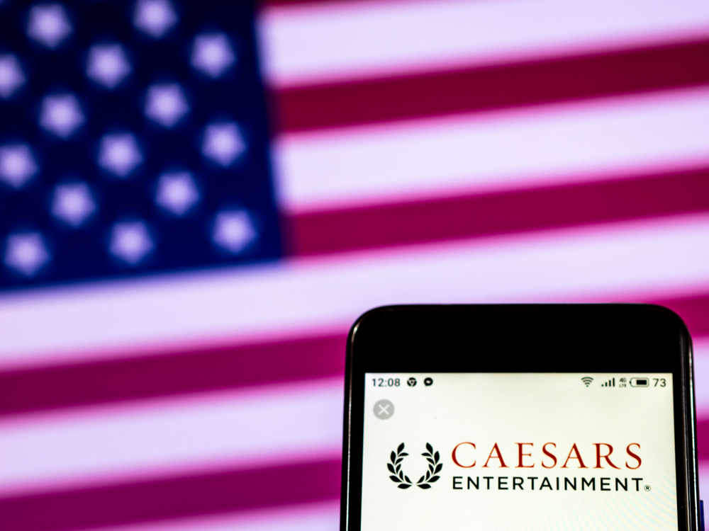 Caesars Entertainment logo on phone in front of US flag