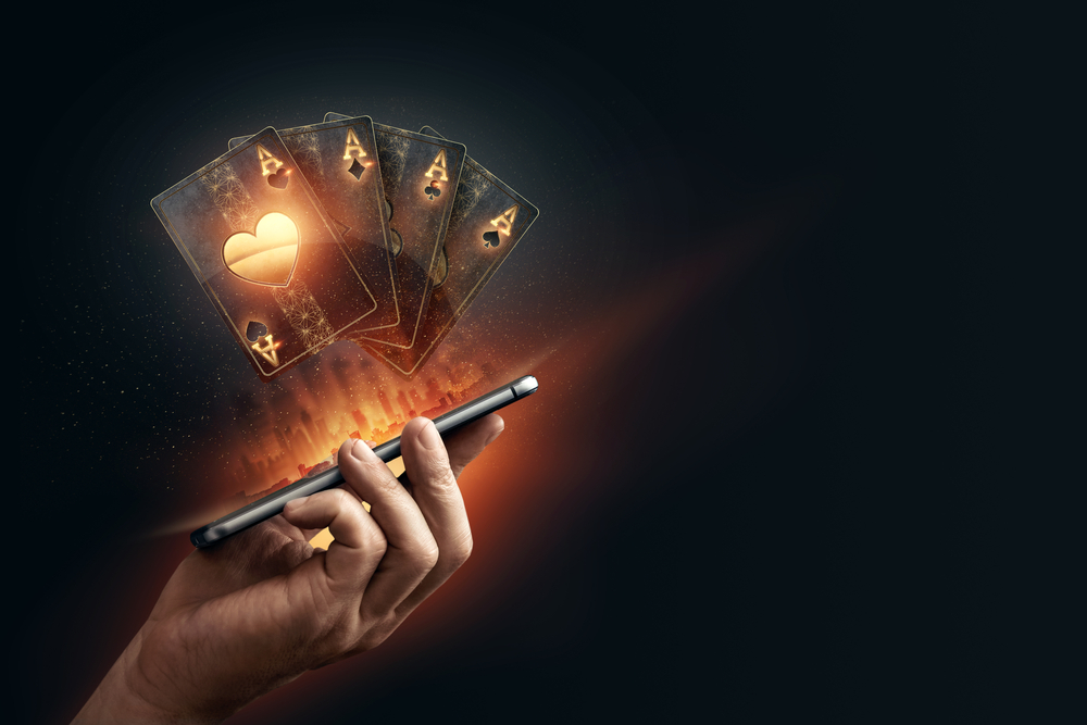 online casino concept with hologram of playing cards hovering above hand holding mobile phone