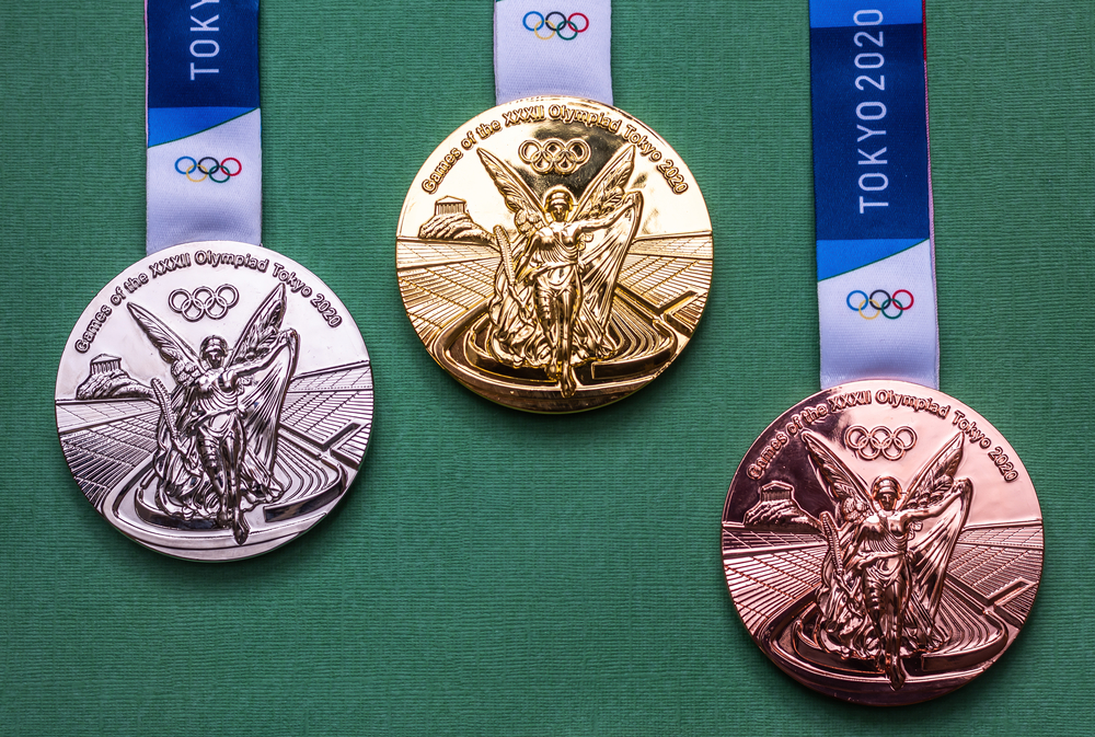 gold, silver, and bronze 2020 Tokyo Olympics medals against green background