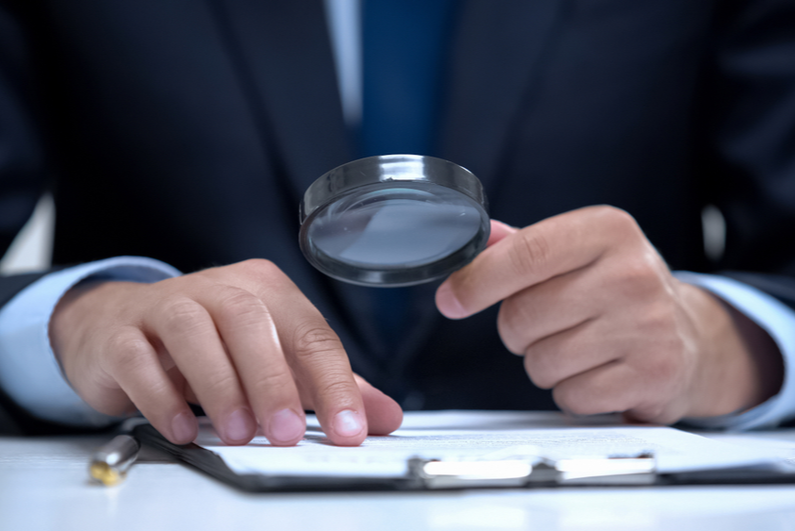 Businessman reading document through magnifying glass