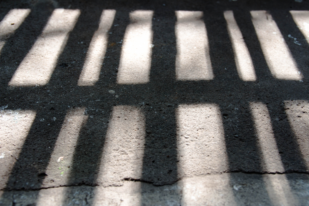 shadow of prison bars on ground