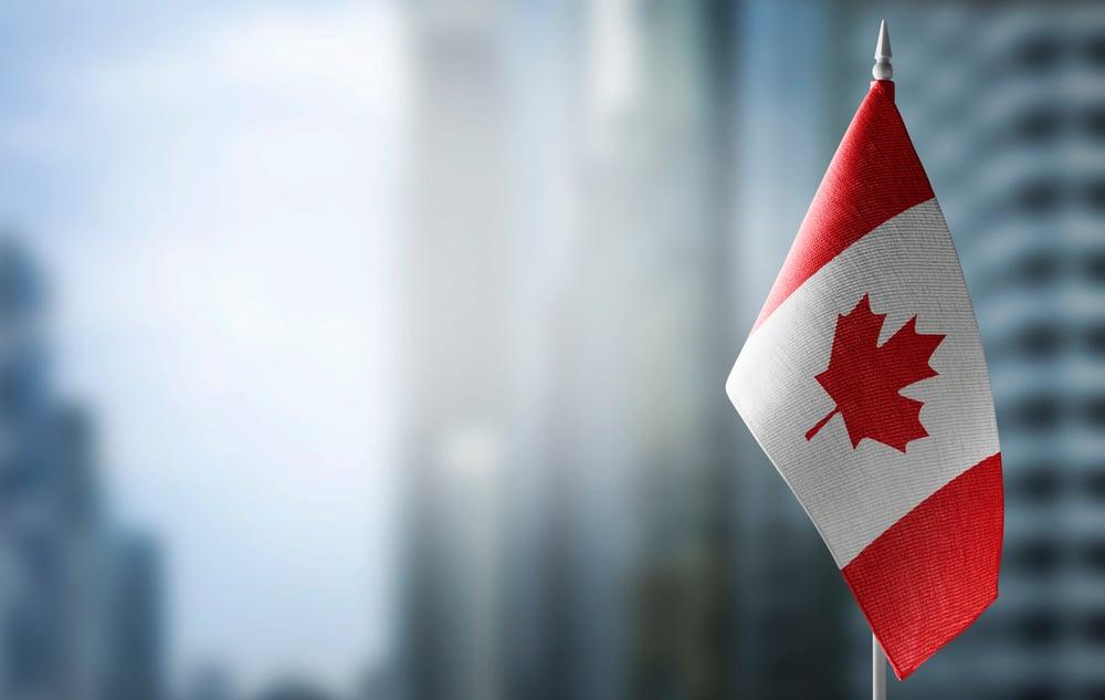 Canada flag against blurred city background