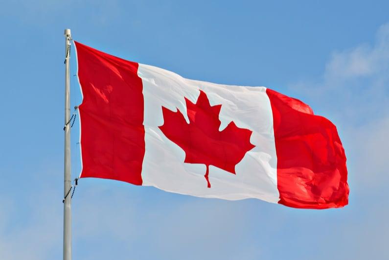 Canadian flag flying against a blue sky backdrop