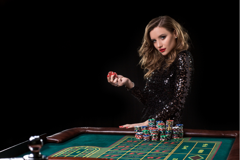 Babae na may hawak na chips sa isang table ng roulette