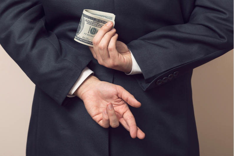 Businessman holding money and crossed fingers behind his back