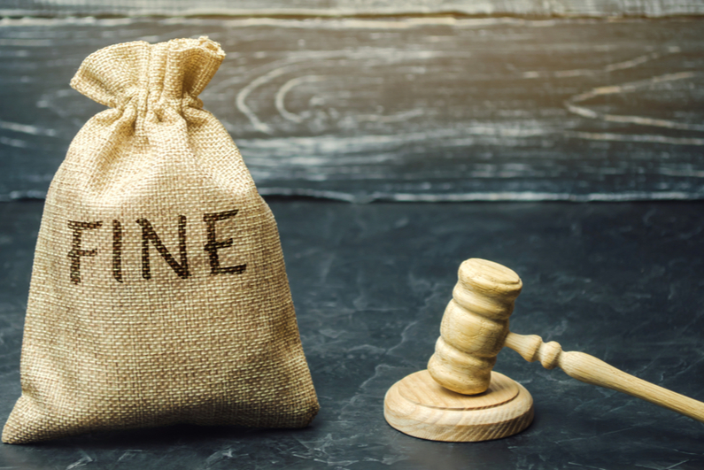 """Judge's gavel next to a money bag labeled """"FINE"""""""