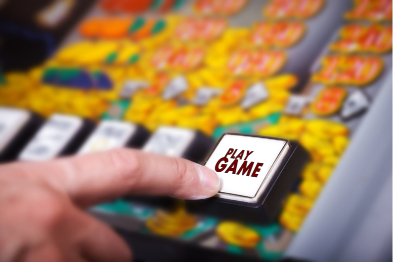 hand presses play game button on slot machine