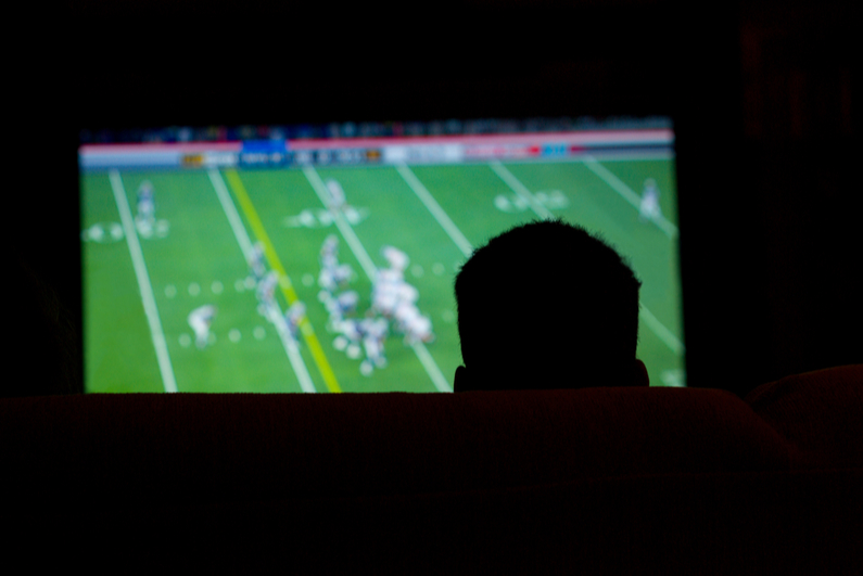 Silhouette of man watching football
