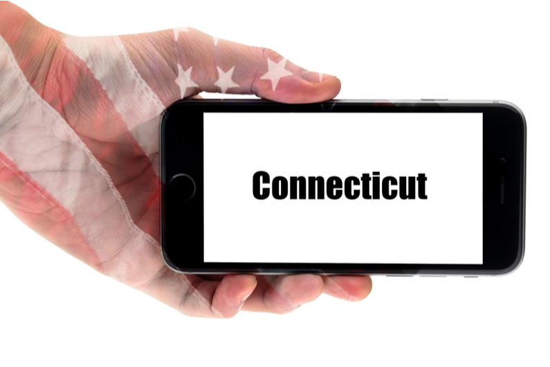 hand holding smartphone with the word Connecticut on screen