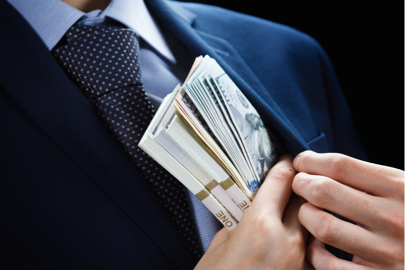 male in suit hiding wads of dollar bills in his jacket